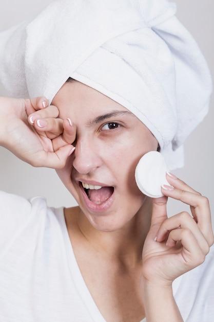 Mujer sonriente con almohadillas de algodón Foto gratis