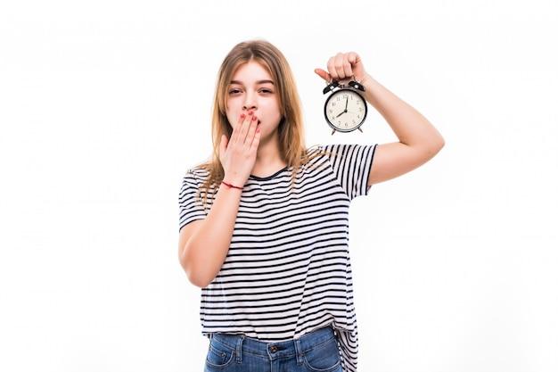 Mujer sonriente en anteojos con reloj despertador Foto gratis