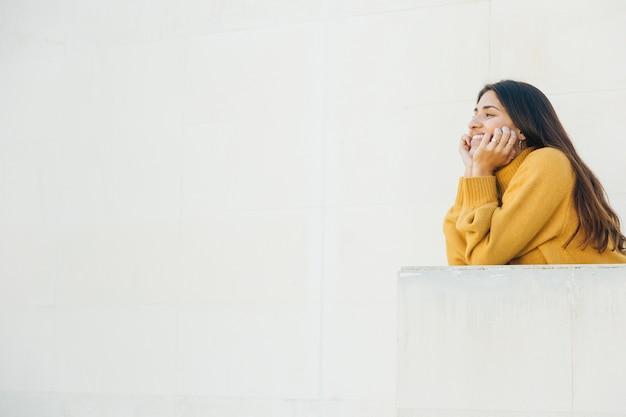 Mujer sonriente apoyado en el balcón mirando a otro lado Foto gratis