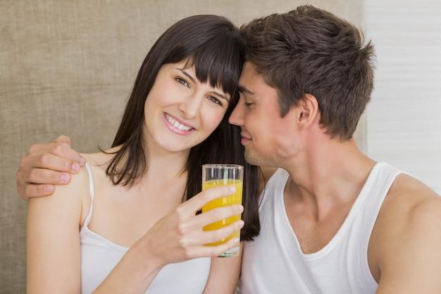 Mujer sonriente bebiendo jugo mientras el hombre abrazando en la cama en el dormitorio Foto Premium