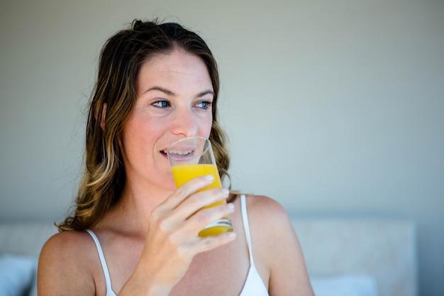 Mujer sonriente bebiendo un vaso de jugo de naranja en su habitación Foto Premium