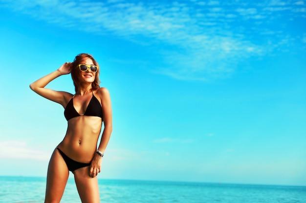 Mujer sonriente en bikini disfrutando del cielo azul Foto gratis