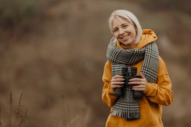 Mujer sonriente con binoculares Foto gratis