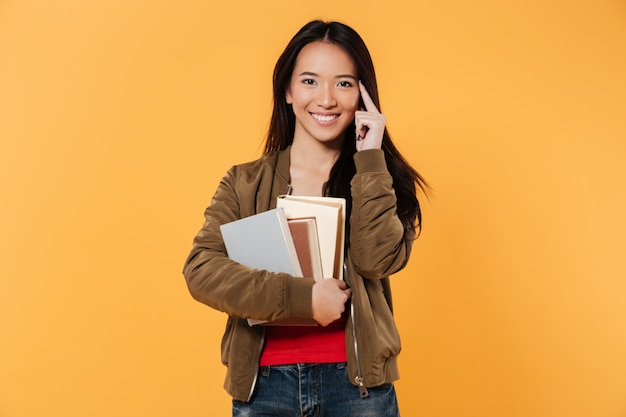 Mujer sonriente en chaqueta sosteniendo libros mientras mira a la cámara Foto gratis