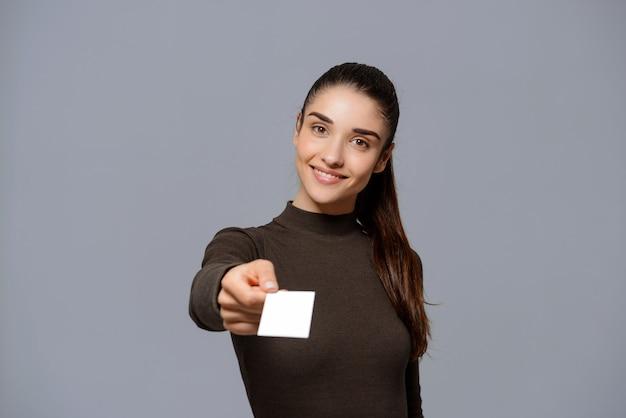 La mujer sonriente le da su tarjeta de visita Foto gratis