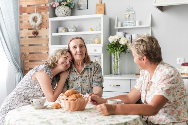 Mujer sonriente desayunando con su madre y su abuela en casa Foto gratis