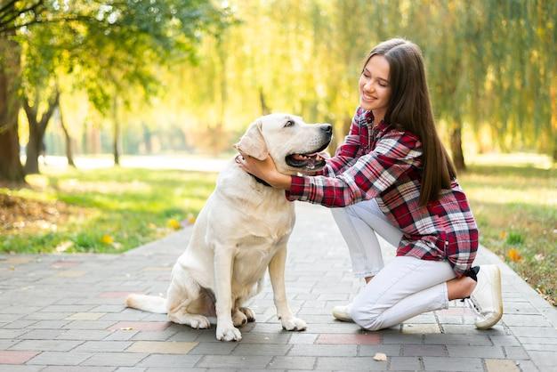 Mujer sonriente enamorada de su perro Foto gratis