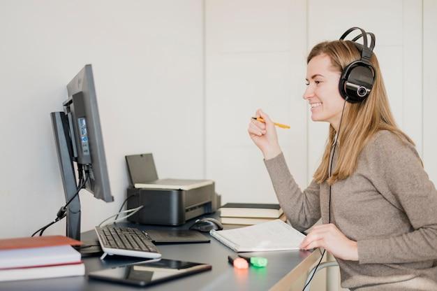 Mujer sonriente en el escritorio con auriculares y una clase en línea Foto gratis