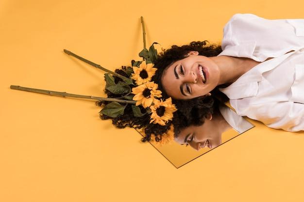 Mujer sonriente étnica atractiva con las flores en el espejo Foto gratis