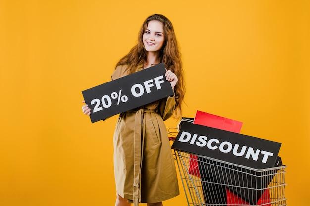 Mujer sonriente en gabardina con signo de descuento del 20% y coloridas bolsas de compras en carro aislado sobre amarillo Foto Premium