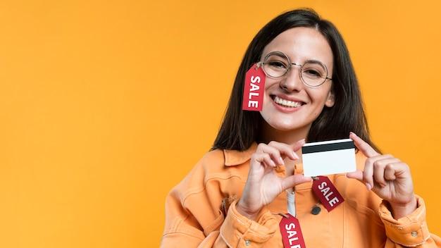 Mujer sonriente con gafas y chaqueta con etiqueta de venta y tarjeta de crédito Foto gratis