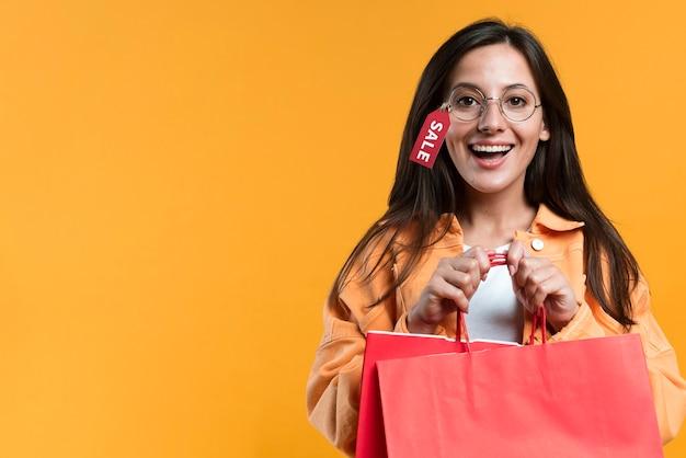 Mujer sonriente con gafas con etiqueta y sosteniendo la bolsa de compras Foto gratis