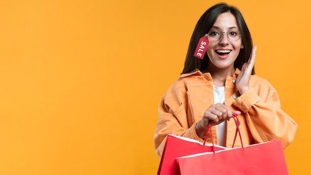 Mujer sonriente con gafas con etiqueta de venta y sosteniendo bolsas de la compra. Foto gratis
