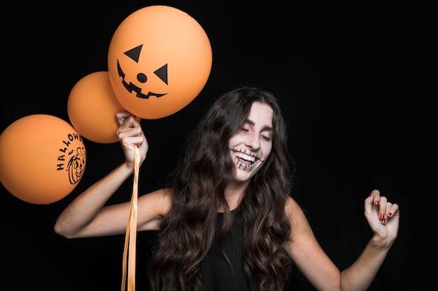 Mujer sonriente con globos de halloween y baile Foto gratis