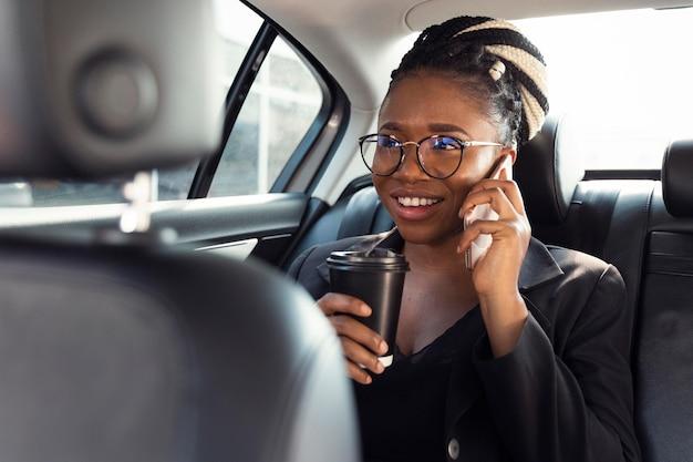 Mujer sonriente hablando por teléfono en el asiento trasero del coche mientras toma un café Foto gratis