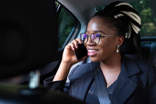 Mujer sonriente hablando por teléfono inteligente mientras está en su coche Foto gratis