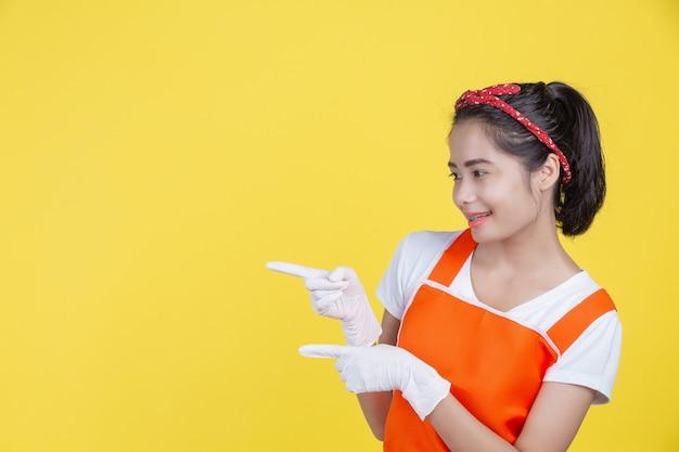 Mujer sonriente hermosa que lleva guantes de goma amarillos en un amarillo. Foto gratis