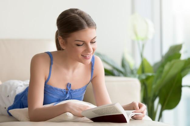 Mujer sonriente joven que lee el libro interesante en el sofá en casa Foto gratis