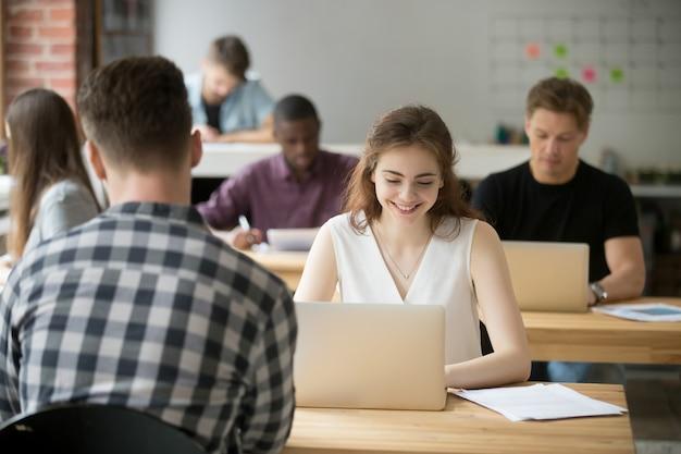 Mujer sonriente joven que trabaja en la computadora portátil en espacio de oficina coworking Foto gratis