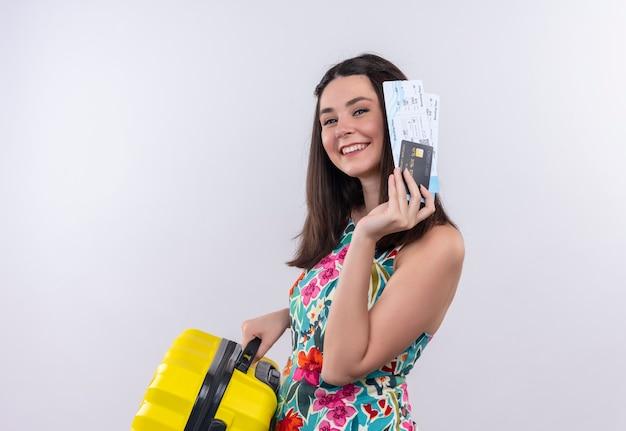Mujer sonriente joven viajero con billetes de avión y maleta en pared blanca aislada Foto gratis