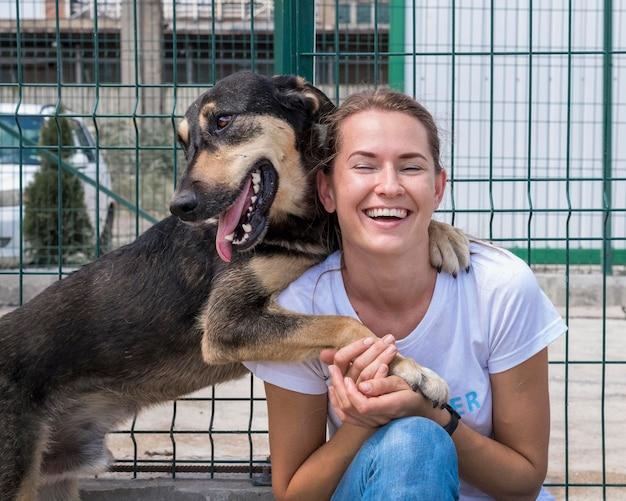 Mujer sonriente jugando en el refugio con perro esperando ser adoptado Foto gratis