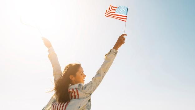 Mujer sonriente levantando las manos con la bandera de estados unidos Foto gratis