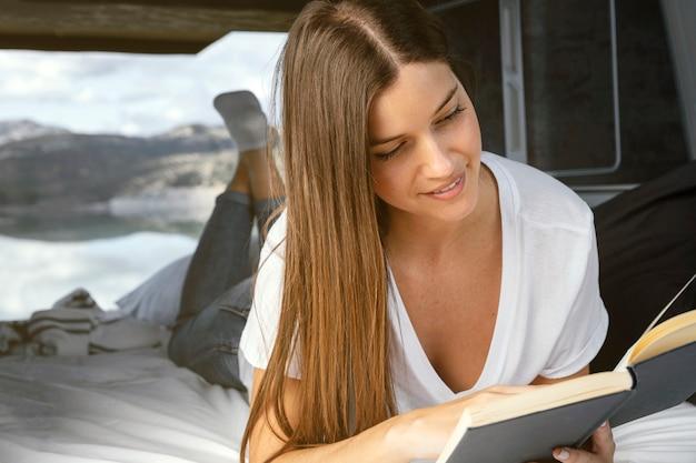 Mujer sonriente leyendo concepto de viaje por carretera Foto gratis