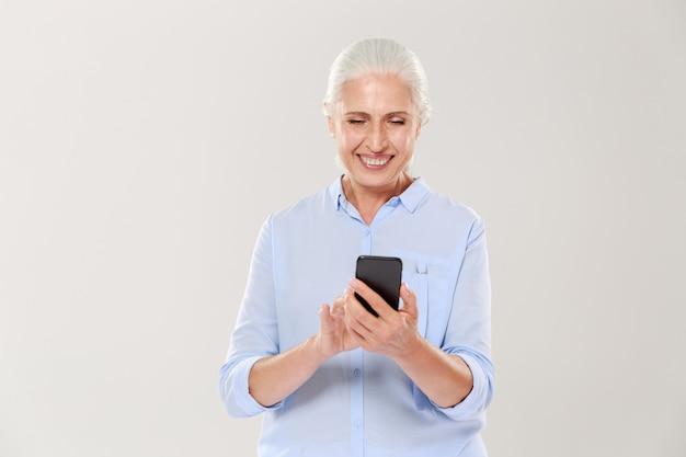 Mujer sonriente madura que usa el teléfono inteligente aislado Foto gratis