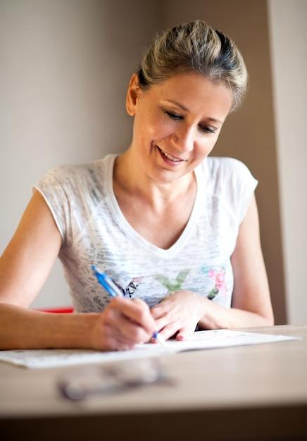 Mujer sonriente con el pelo atado tomando notas Foto Premium