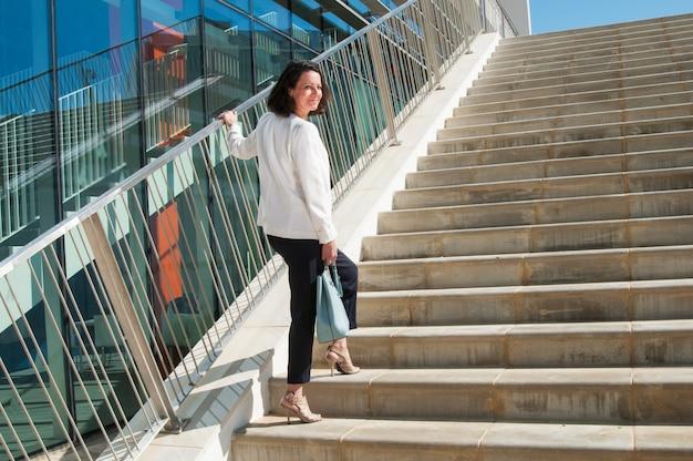 Mujer sonriente de pie en las escaleras, volviendo la cabeza hacia la cámara Foto gratis