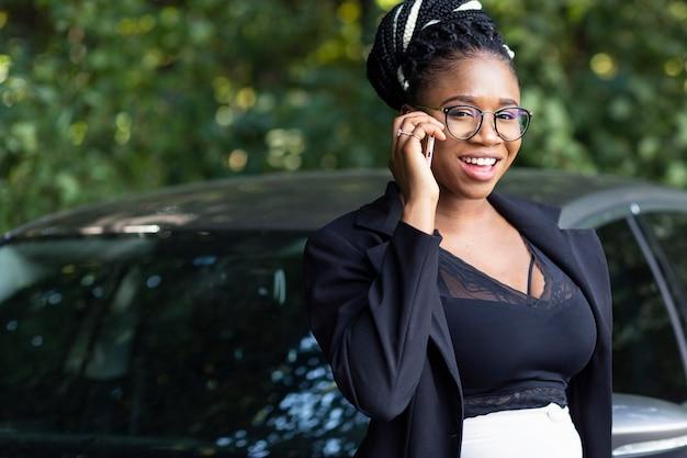 Mujer sonriente posando junto al coche mientras habla por teléfono inteligente Foto gratis