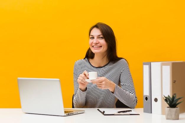 Mujer sonriente posando en su escritorio mientras sostiene una taza de café Foto gratis