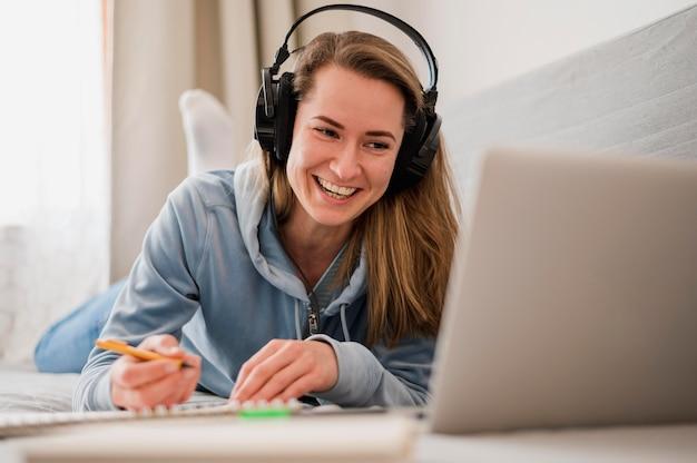 Mujer sonriente que asiste a una clase en línea Foto gratis