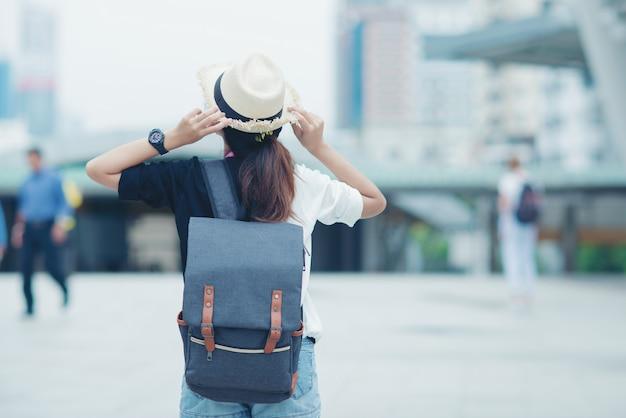 Mujer sonriente que camina al aire libre, señora joven que admira vista de la ciudad con la calzada y edificios en fondo. Foto gratis