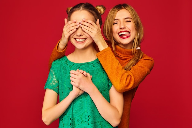 Mujer sonriente que cubre los ojos con las manos a su amiga Foto gratis
