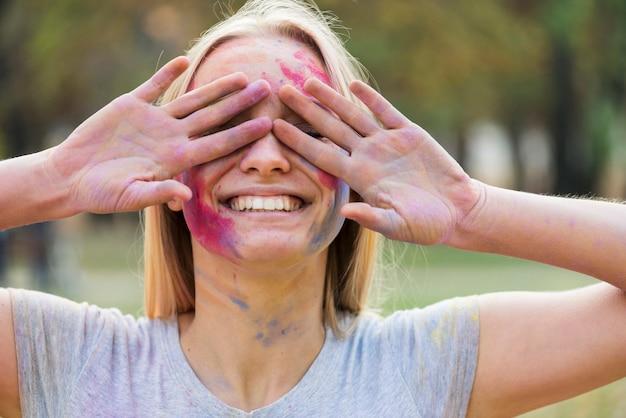 Mujer sonriente que cubre sus ojos en el festival Foto gratis