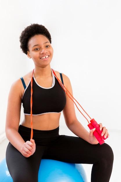 Mujer sonriente que ejercita con saltar la cuerda Foto gratis