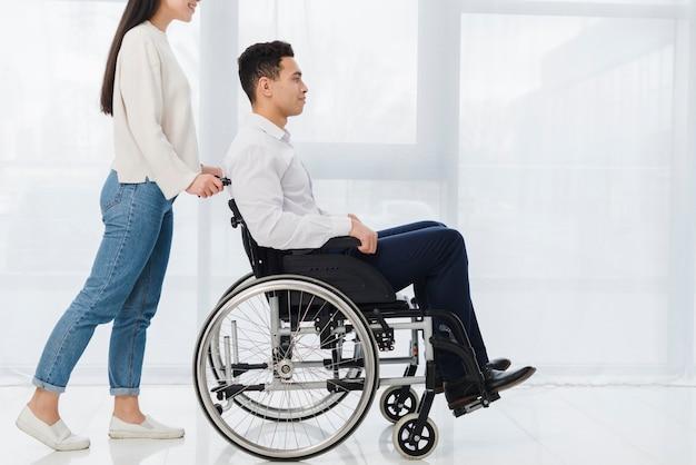 Mujer sonriente que empuja al hombre joven que se sienta en silla de ruedas Foto gratis