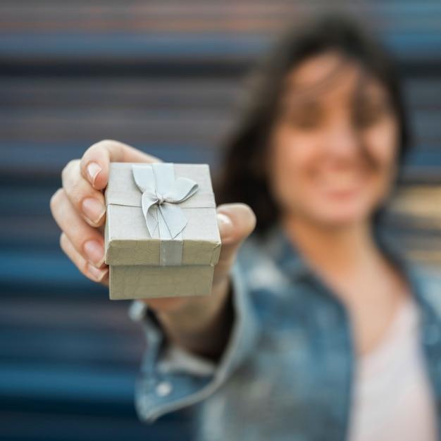 Mujer sonriente que muestra la actual caja Foto gratis