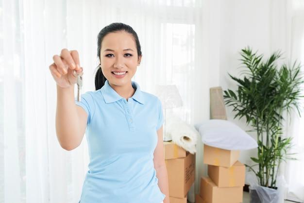 Mujer sonriente que muestra la llave del apartamento nuevo Foto gratis