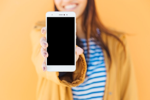 Mujer sonriente que muestra la pantalla en blanco del teléfono inteligente contra el fondo amarillo Foto gratis