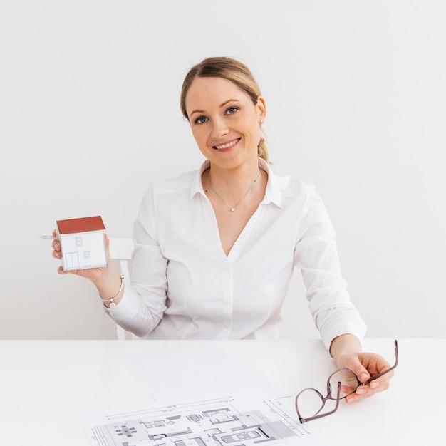 Mujer sonriente que muestra el pequeño modelo de casa de papel en el lugar de trabajo Foto gratis
