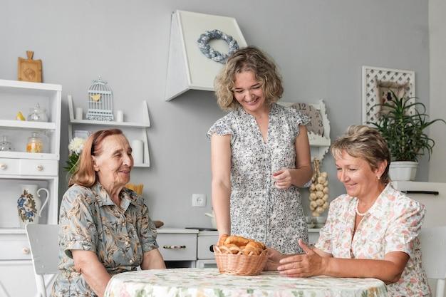 Mujer sonriente que pone la cesta de mimbre de croissant en la mesa frente a una mujer madura y una mujer mayor Foto gratis