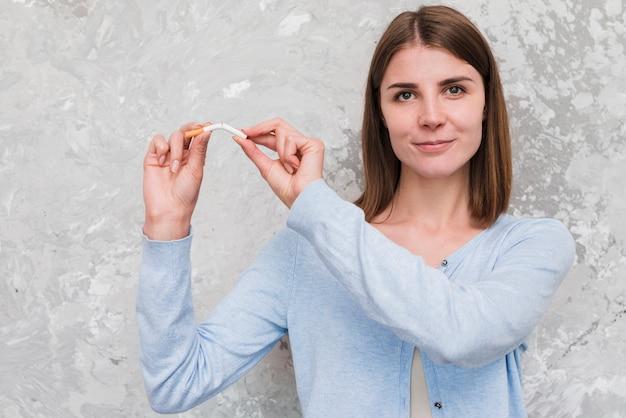 Mujer sonriente que rompe el cigarrillo delante de la pared resistida Foto Premium
