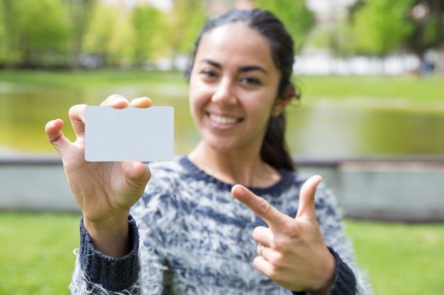Mujer sonriente que señala en la tarjeta de visita en blanco en parque de la ciudad Foto gratis