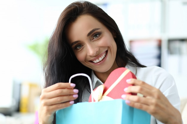 Mujer sonriente que sostiene la caja en forma de corazón Foto Premium