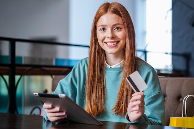 Mujer sonriente que sostiene la tarjeta y la tableta de crédito Foto gratis
