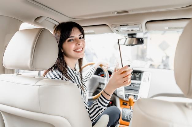 Mujer sonriente sentada al volante de un coche bebiendo café helado Foto Premium