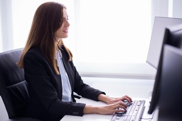 Mujer sonriente sentada escribiendo en un ordenador Foto gratis