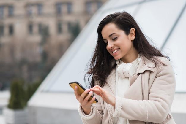 Mujer sonriente con smartphone Foto gratis